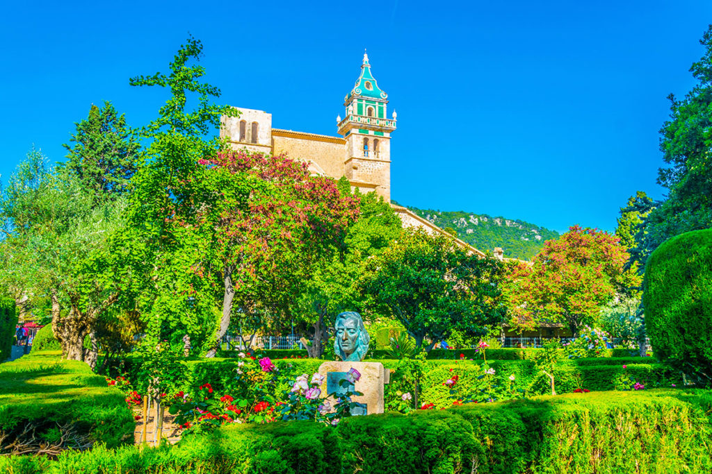 Dawny klasztor Real Cartuja de Jesús de Nazaret (kat. Cartoixa de Valldemossa). Na pierwszym planie przypałacowe ogrody i pomnik Fryderyka Chopina w Valldemossie.